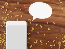 Smartphone, thought bubble, voice command, alphabet noodles, coo. King app on wooden background royalty free stock photo