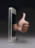 Smartphone with thumb up symbol on dark background. Royalty Free Stock Photos