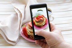 Smartphone tiró la foto de la comida - crepes para el desayuno con las fresas Imágenes de archivo libres de regalías