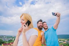Smartphone together. Friends having fun on roof, take selfie. Ta stock image