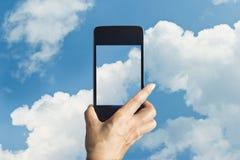 Smartphone toma las fotos de la nube en fondo del cielo azul Imagen de archivo libre de regalías
