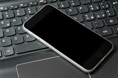 Smartphone on top of laptop stock photo