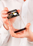 Smartphone with transparent screen in human hands. Royalty Free Stock Image