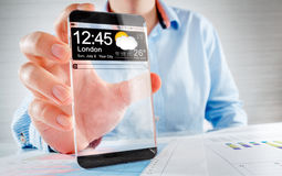 Smartphone with transparent screen in human hands. Royalty Free Stock Photo