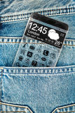 Smartphone with a transparent screen in a pocket of jeans. Stock Photo