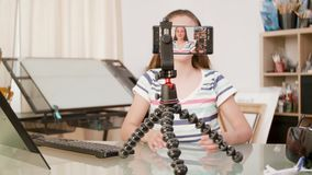 Smartphone on a tripod filming a young girl talking