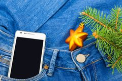 Smartphone and twig Christmas tree with ornament. White mobile phone in pocket of jeans and twig Christmas tree with Christmas ornament Stock Images