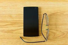 Smartphone und Augenglas geschlossen oben auf dem Boden stockfotografie