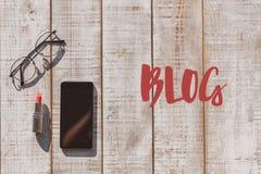 Smartphone und Brillen auf Schreibtisch für weiblichen Blogger Lizenzfreie Stockfotografie