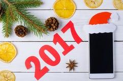 Smartphone und die Aufschrift 2017 auf einem hölzernen Hintergrund, Spitze Stockbilder