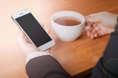 Smartphone und eine Tasse Tee stockbilder