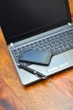 Smartphone und elegante Feder auf einem Laptop Lizenzfreies Stockfoto