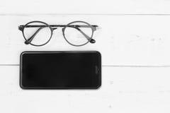 Smartphone und Lesebrille Stockfotos