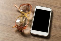 Smartphone und Lesebrille auf einem alten hölzernen Brett lizenzfreie stockfotos