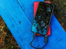 Smartphone und powerbank auf einem Brett Stockfotografie