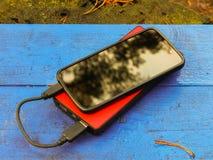 Smartphone und powerbank auf einem Brett Lizenzfreies Stockbild