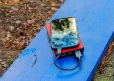 Smartphone und powerbank auf einem Brett Stockfotos