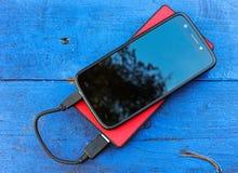 Smartphone und powerbank auf einem Brett Stockbilder