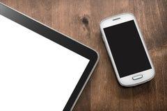 Smartphone und Tablet auf einer Wohnzimmer-Tabelle Lizenzfreie Stockbilder