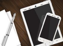 Smartphone und Tablette auf Holztisch Stockbilder