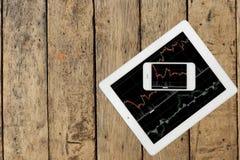 Smartphone und Tablette mit Diagramm auf hölzerner Tabelle stockfoto