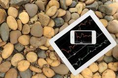 Smartphone und Tablette mit Diagramm auf Steinboden lizenzfreies stockbild