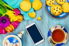 Smartphone und Tasse Tee mit Plätzchen Lizenzfreie Stockbilder