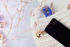 Smartphone und Winterhut auf weißem Hintergrund Stockfoto