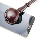 Smartphone under judge gavel - close up studio shot on white Stock Images