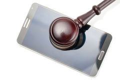 Smartphone under judge gavel - studio shot on white Stock Image