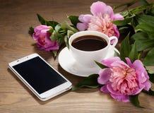 Smartphone, une tasse de café et de fleurs sur la vieille table image stock