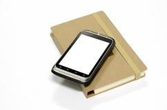 Smartphone usado com livro de nota Foto de Stock