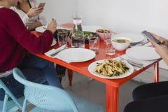 Smartphone usando-se na tabela de jantar fotografia de stock
