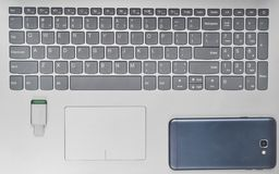 Smartphone usb-exponeringsdrev på bärbar datortangentbordet Top beskådar Moderna apparater och grejer Royaltyfri Foto