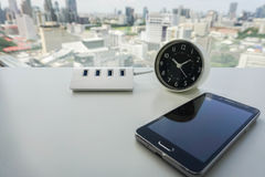Smartphone with USB hub and modern minimal clock Stock Image