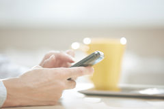 Smartphone user. Hands of smartphone user at lunch Royalty Free Stock Images