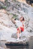 Smartphone usin молодой женщины на озере Стоковые Изображения