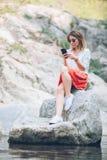 Smartphone usin молодой женщины на озере Стоковое Изображение