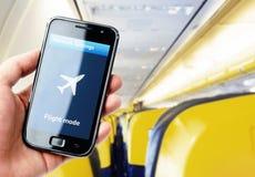 Smartphone van de handholding binnen het vliegtuig stock afbeelding