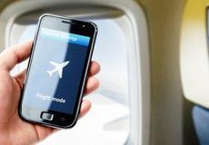 Smartphone van de handholding binnen het vliegtuig stock foto