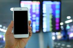 Smartphone van de handholding met de achtergrond van de vluchtraad Royalty-vrije Stock Foto