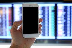 Smartphone van de handholding met de achtergrond van de vluchtraad Royalty-vrije Stock Afbeelding