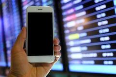 Smartphone van de handholding met de achtergrond van de vluchtraad Royalty-vrije Stock Afbeeldingen