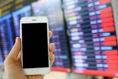 Smartphone van de handholding met de achtergrond van de vluchtraad Stock Afbeeldingen