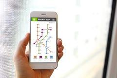 Smartphone van de handholding met de toepassing van de spoorwegkaart Stock Foto's