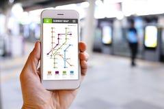 Smartphone van de handholding met de toepassingsachtergrond van de metrokaart Stock Foto's