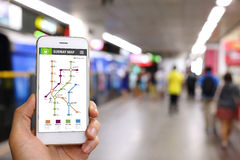 Smartphone van de handholding met de toepassingsachtergrond van de metrokaart Stock Foto