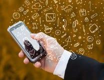 Smartphone van de handholding met hand getrokken media pictogrammen en symbolen Stock Afbeeldingen