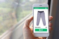 Smartphone van de handholding met het schermwebsite van de sweatpantselektronische handel Royalty-vrije Stock Afbeeldingen