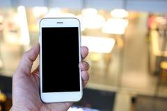 Smartphone van de handholding met nacht lichte achtergrond Stock Afbeelding